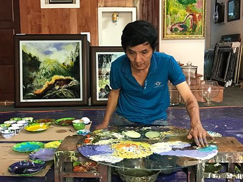 Họa sĩ Đoàn Việt Tiến đang vẽ trên một tấm kính tại xưởng vẽ ở nhà. Ảnh: Kim Anh