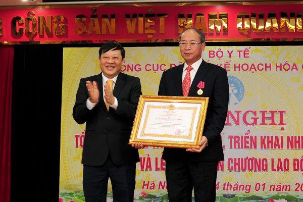 Thừa ủy quyền Chủ tịch nước, Thứ trưởng Bộ Y tế Nguyễn Viết Tiến trao tặng Huân chương Lao động hạng Nhất cho ông Nguyễn Văn Tân, nguyên Phó Tổng cục trưởng phụ trách Tổng cục DS-KHHGĐ về những đóng góp cho sự nghiệp DS-KHHGĐ. Ảnh: Chí Cường
