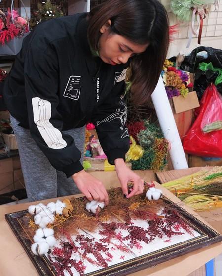 Chị Lan Anh, chủ cửa hàng hoa ở đường Bưởi (Hà Nội) sắp hoa cho khách. Ảnh: Nguyễn Phượng.