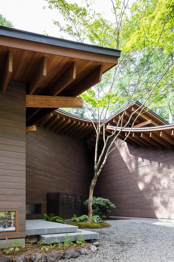 Mái nhà chính là điểm nhấn thẩm mỹ đặc biệt của toàn bộ công trình. Mái gồm hai lớp, phía trên màu xám và phía dưới là những thanh gỗ dán veneer được xếp thẳng liên tục tạo thành một hình học ấn tượng.