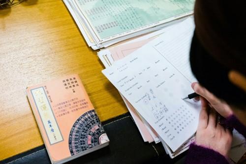 Thầy phong thủy sử dụng biểu đồ và bảng tính toán để dự đoán tương lai.