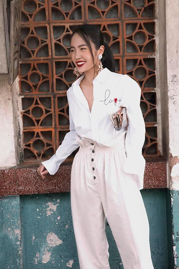 Thanh Vy thể hiện sự phá cách khi kết hợp quần lưng cao cùng sơ mi thêu. Hoa tai to bản được top 6 Asias Next Top Model 2018 chọn lựa để tạo điểm nhấn cho tổng thể.