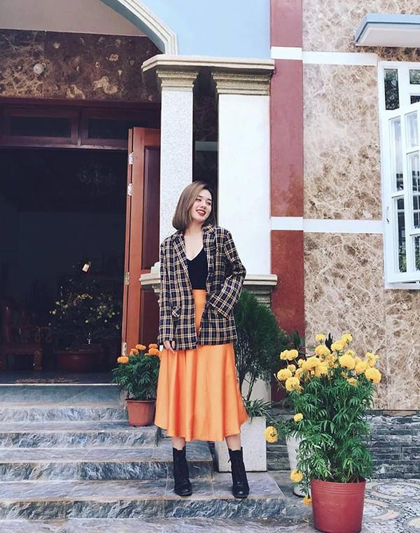 Trâm Anh The Face phối đồ rực rỡ với blazer kẻ sọc ca rô, đầm xoè vàng cam và áo thun đen đồng điệu cùng tông màu của bốt da.