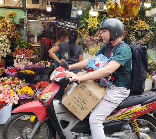 Một khách hàng tranh thủ mua hoa sớm tặng người yêu nhân ngày Lễ tình nhân