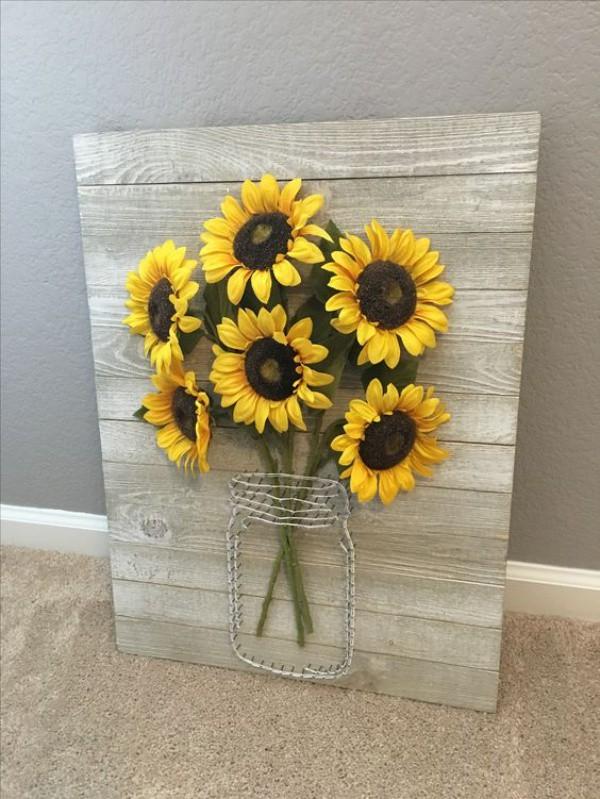 Chọn những bông hướng dương bằng giấy, vải hay nhựa để gắn chúng thành hình quả bóng hoa và treo lên cửa sổ. Cách trang trí này không mới nhưng vẫn mang lại hiệu quả vô cùng ấn tượng và bắt mắt cho ngôi nhà của bạn.