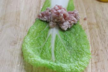 Bước 2: Uớp thịt ới chút gia vị, hạt tiêu và hành băm. Trải từng lá cải thảo ra, cho thịt vào cuộn lại như gói nem và buộc lại bằng hành lá.