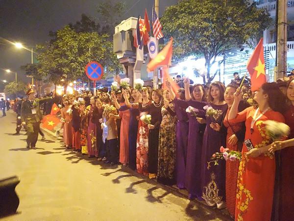 Đoàn phụ nữ phường Mễ Trì mặc áo dài, cầm cờ hoa vẫy chào Tổng thống Trump
