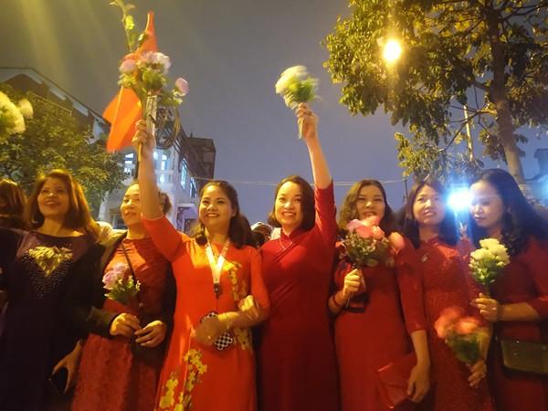 Đoàn phụ nữ phường Mễ Trì mặc áo dài, cầm cờ hoa vẫy chào Tổng thống Trump. Ảnh Lê Bảo