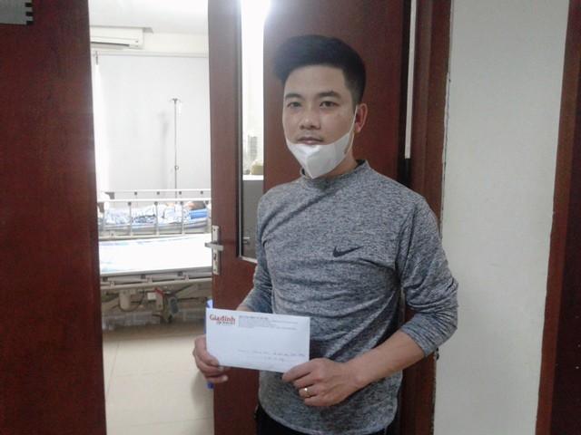 Đại diện gia đình cháu Hưng nhận số tiền 4.900.000 đồng do bạn đọc Báo Gia đình & Xã hội ủng hộ.