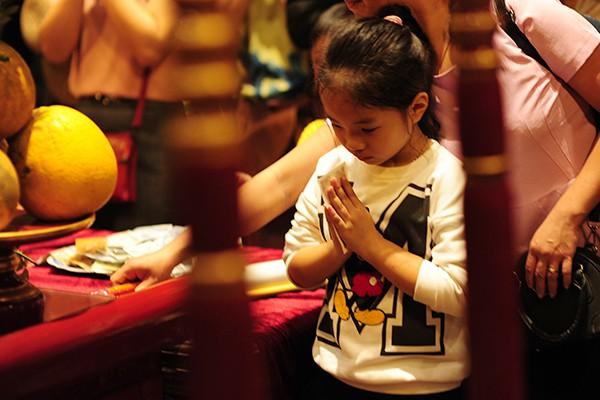 Một cô bé với dáng vẻ thành tâm cầu nguyện không kém gì người lớn.