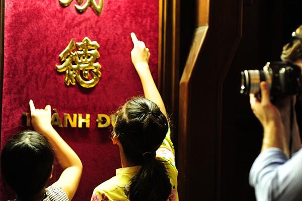 Các cô bé đua nhau viết tên mình cùng với lời cầu nguyện lên các khung chữ thể hiện sự thành đạt trong học hành.