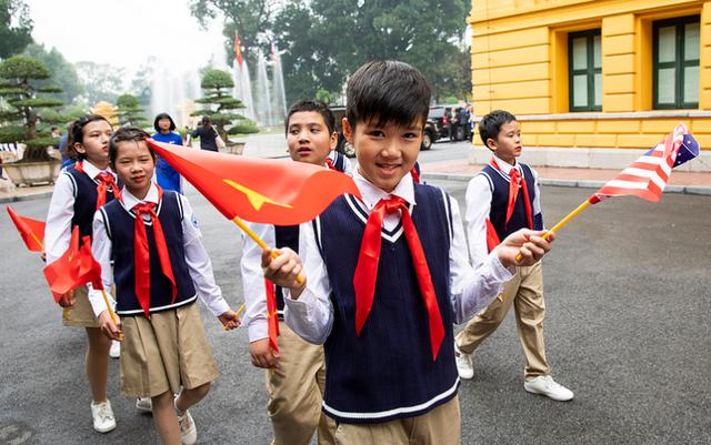 Các em học sinh cầm cờ chào đón các nguyên thủ quốc gia (ảnh tư liệu)