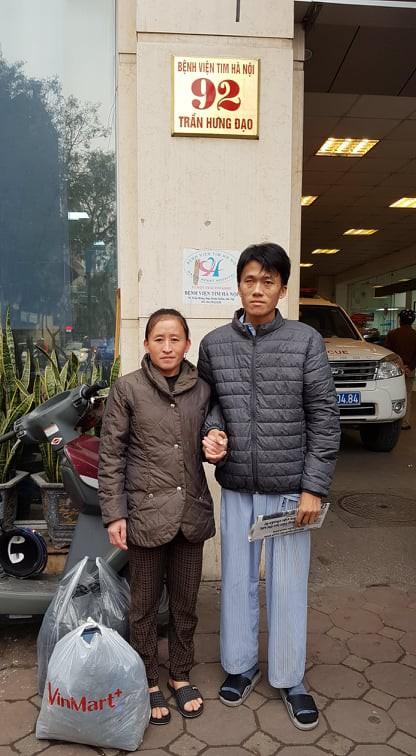 Vợ Sùng A Khua dìu chồng đi nhận quà của độc giả Báo Gia đình & xã hội gửi tặng.