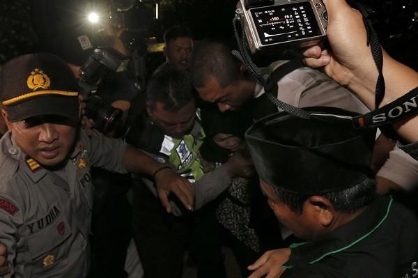 Cảnh sát hộ tống Aisyah đi qua đám đông. (Ảnh: AP)