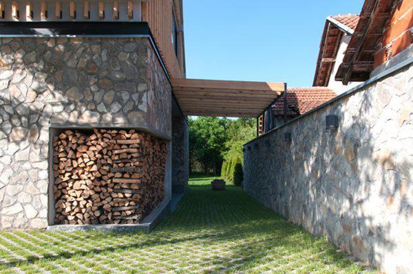 Lối đi bên hông và bao quanh nhà được lát gạch lỗ, trồng xen cỏ xanh mượt.