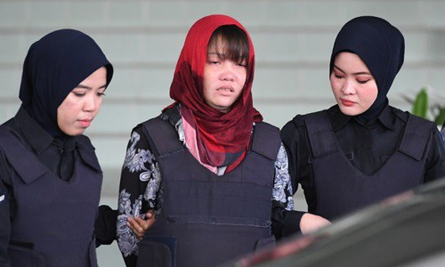 Cảnh sát áp giải Đoàn Thị Hương (giữa) rời tòa án ở Kuala Lumpur, Malaysia hôm 14/3. Ảnh: AFP.