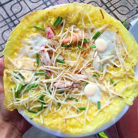Bánh xèo chảo: Không chỉ có giá, thịt, bánh xèo chảo ở Nha Trang đặc biệt và đa dạng hương vị hơn bởi được thêm cả tôm, mực… hải sản của miền biển. Tùy khẩu vị cá nhân, bạn có thể lựa chọn tôm hoặc mực để chế biến. Nhiều quán bánh xèo tại Nha Trang còn cho trứng cút hoặc trứng gà vào giữa, trông khá giống bánh căn. Ảnh: Foody.