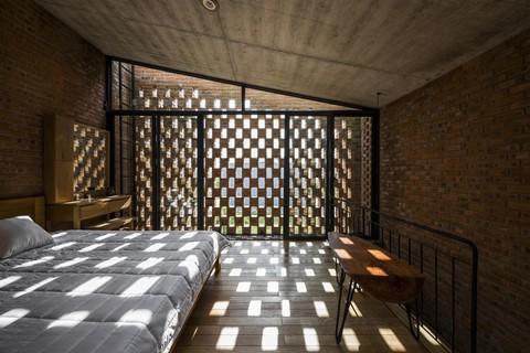 Phòng ngủ chính cũng được chia tách riêng, với lớp tường gạch có ô thoáng, vừa có ánh sáng tự nhiên, thoáng khí, vừa đảm bảo sự riêng tư.