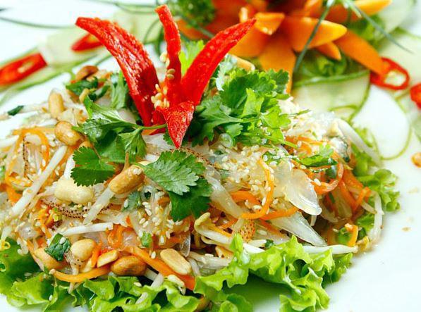 Cho nộm sứa ra đĩa trang trí bằng 1 số rau mùi và ớt chín
