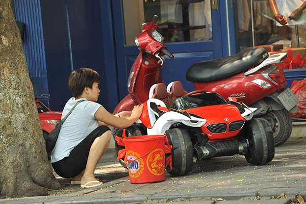 Tranh thủ lau rửa xe để phục vụ các khách hàng nhí.