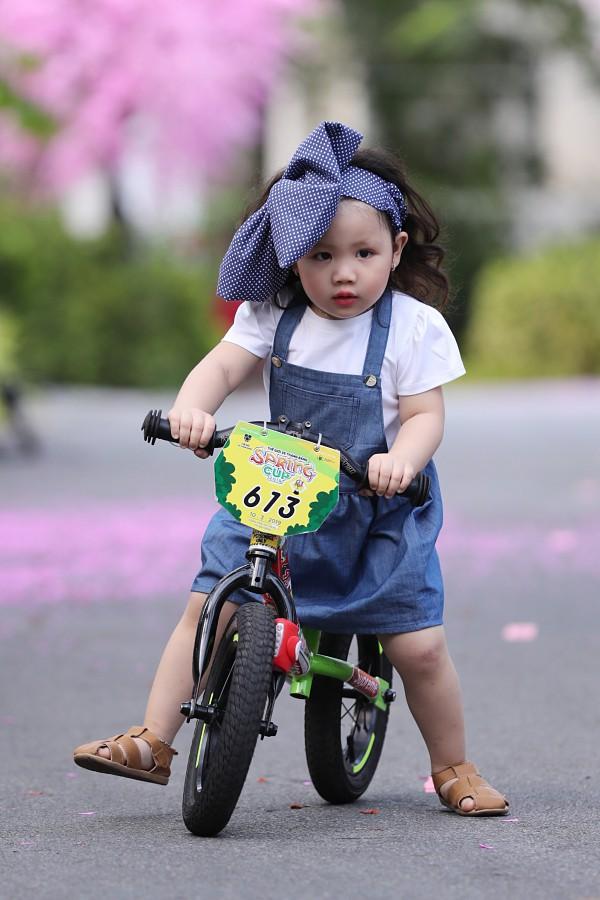 Mẫu nhí An Hy đạp xe diễn thời trang. Vẻ đáng yêu của cô bé chỉ hơn hai tuổi khiến khán giả thích thú.
