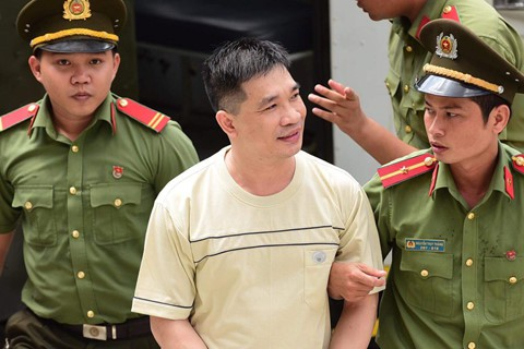 Văn Kính Dương cười tươi khi được dẫn giải đến tòa ngày 7/5. Ảnh: Lê Quân.