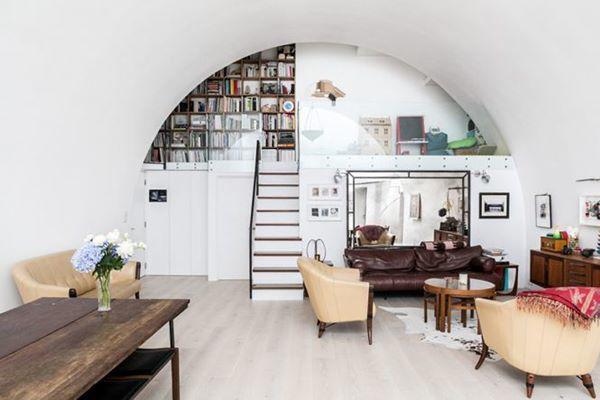 Phòng khách ngăn nắp và hiện đại với mái vòm cong. Để tiết kiệm diện tích sử dụng, phần trần được thiết kế như một gác xép nhỏ để chứa sách và phòng đọc.