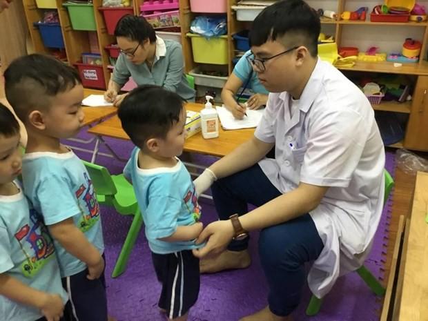 Các bác sỹ khám cho trẻ trong Chương trình khám sàng lọc bất thường bộ phận sinh dục cho bé trai. (Ảnh: PV/Vietnam+)