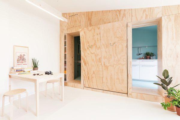 Hai bức tường ốp ván ép giúp che giấu đồ đạc, giường đôi, tủ quần áo, cửa trượt che nhà bếp và phòng tắm bên trong.