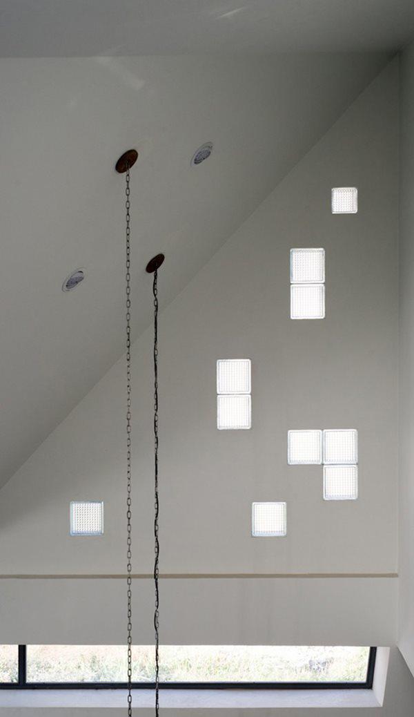 Những ô kính ngẫu hứng trên bức tường phòng khách vừa giúp lấy sáng vừa như một cách trang trí đơn giản nhưng mang lại hiệu quả cao.