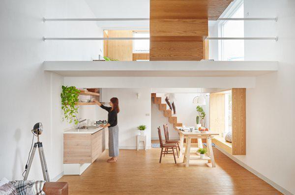 Khu vực bếp nằm ngay dưới gác lửng, bàn ăn được đặt cạnh khung cửa sổ lớn, chiếm gần trọn vẹn bức tường đối diện bếp.