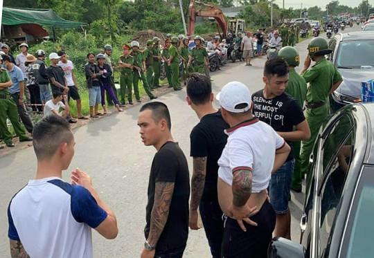 Nhóm người xăm trổ đứng bao vây ôtô chở công an hôm 12/6. Ảnh: Thái Hà.