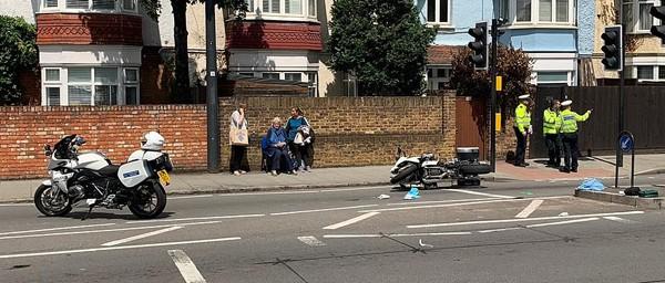 Cụ bà được người dân đỡ lên ngồi nghỉ sau tai nạn.