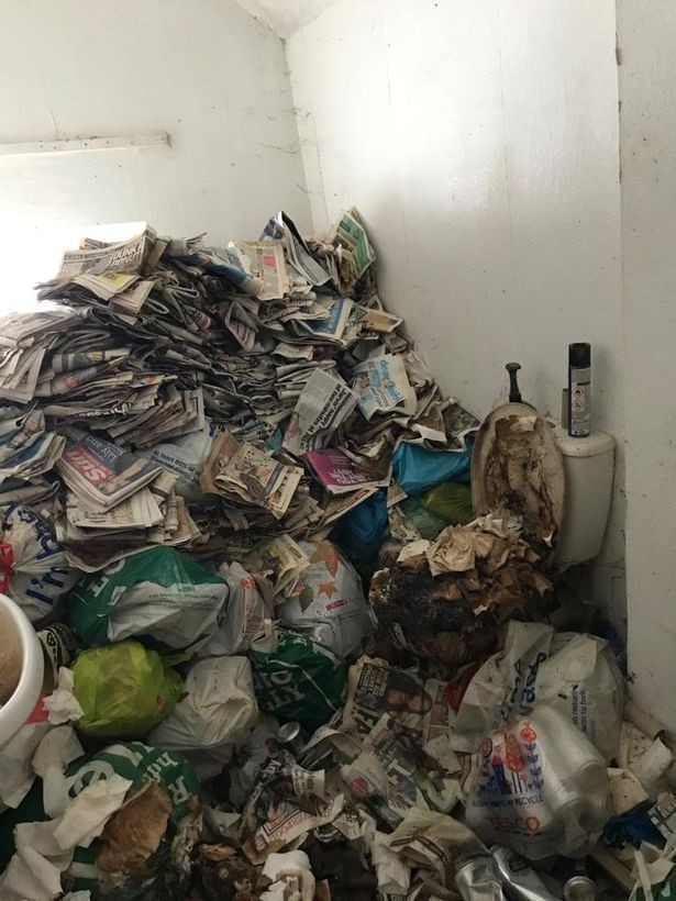 Phòng tắm bị bôi trét đầy phân bên cạnh đống báo cũ.