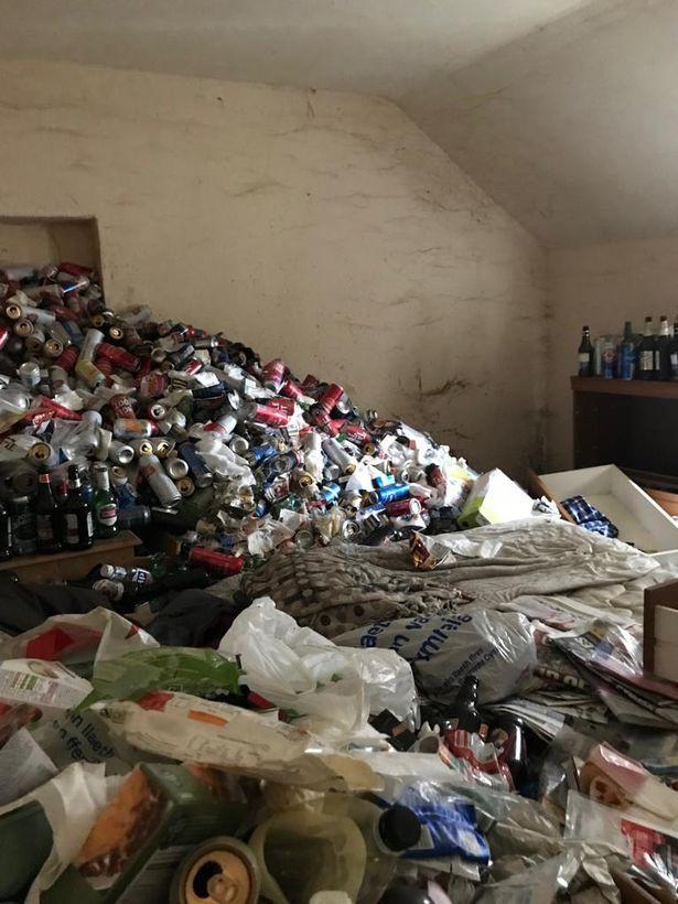 Núi lon bia bên trong căn nhà như ở bãi rác