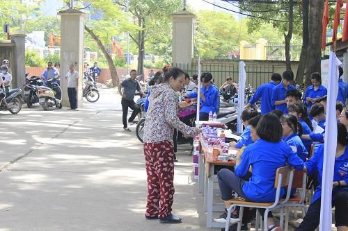 Phụ huynh nhận nước uống miễn phí từ các tình nguyện viên chương trình Tiếp sức mùa thi.