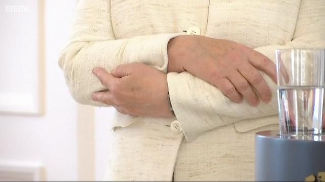 Hai tay bà Merkel khoanh chặt khi chứng kiến lễ tuyên thệ của tân Bộ trưởng Tư pháp Đức. Ảnh cắt từ clip BBC