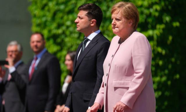Thủ tướng Đức mím chặt môi trong khi cả người run lẩy bẩy giữa lễ chào cờ trong buổi tiếp tổng thống Ukraine hôm 18/6. Khi run rẩy, bà cũng liên tục nắm chặt hai bàn tay với nhau.