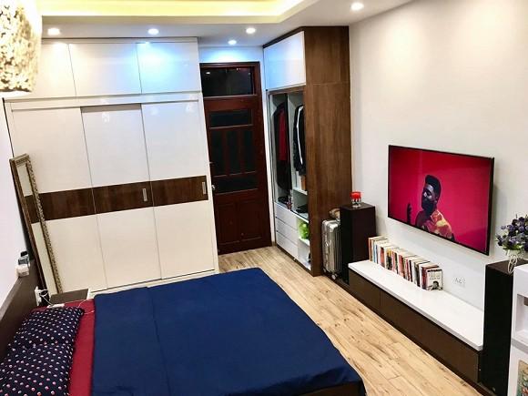 Phòng ngủ ngăn nắp, gọn gàng với hệ thống tủ được ốp vào tường cao đến trần nhà