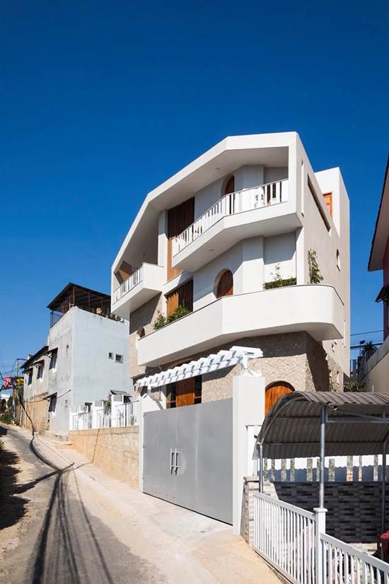 Mặt sau là khu dân cư tự phát, ngôi nhà cũng mang diện mạo bình dị hơn với bức tường nhà sáng màu cùng những ô cửa gỗ rộng vừa phải, ẩn hiện đằng sau hàng rào hay cánh cổng.
