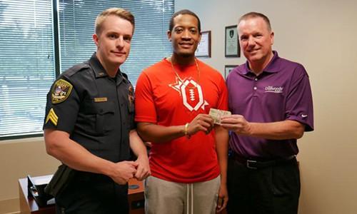 Anh Randrell Lewis, giữa, giao nộp số tiền nhặt được cho cảnh sát Dunwoody. Ảnh: Dunwoody Police