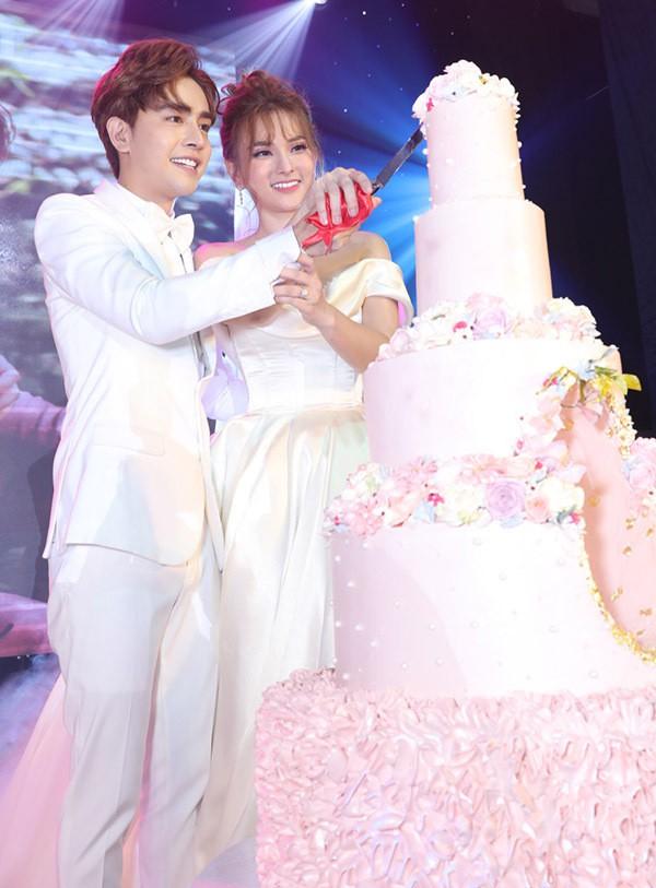 Hai người rạng rỡ tay trong tay cắt bánh cưới...