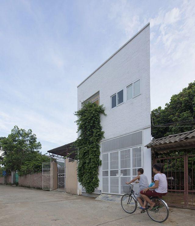 """Tọa lạc tại Thạch Thất, Hà Nội, căn nhà được xây trên phần góc xéo cắt ra từ một mảnh đất lớn, hình dạng méo mó và chật chội.      Ở khu vực ngoại thành, người ta thường xây nhà trên những mảnh đất rộng, vuông vắn nên những miếng đất xấu như thế này ít khi được sử dụng để dựng nhà.        Mảnh đất gần như bị bỏ hoang cho tới khi một thanh niên mua lại nó với giá rẻ.        Khu vực này nằm quá xa trung tâm, trong khi các thợ xây ở địa phương thường gặp khó khăn trong việc đọc bản vẽ kiến trúc, vậy nên mọi thứ đều phải thật tối giản.        Phần tường nhà phía trước được làm bằng gạch thông gió để tạo khoảng trống tại những góc nghiêng và hẹp nhất, trồng cây vào những khe hổng đó để tạo sự riêng tư cho gia chủ.        Khoảng hở này giúp tách biệt không gian sống với mặt đường lớn bên ngoài...        ...vừa lọc khói bụi, tiếng ồn, vừa thông gió và cung cấp ánh sáng tự nhiên cho không gian sống.        Phòng khách hiện đại với bộ sofa màu ghi sáng và thảm trải sàn màu da bò.        Ngay liền kề phòng khách là bếp và phòng ăn.        Sát bếp là giếng trời giúp làm bay bớt mùi khi nấu nướng và đem ánh sáng tự nhiên vào căn phòng.        Bàn ăn mặt bằng kính với những chiếc ghế """"cọc cạch"""" thể hiện cá tính của gia chủ.        Góc đặt tivi và tủ ly được sơn màu vàng tạo điểm nhấn và phân tách không gian giúp tạo cảm giác rộng hơn.        Nội thất tối giản để phòng khách không bị quá ngột ngạt và chật chội.        Tủ quần áo trong phòng ngủ được thiết kế đặc biệt để kê vừa góc xéo của căn nhà.        Góc đọc sách lý tưởng.        Bản vẽ mặt bằng tầng 1.        Bản vẽ mặt bằng tầng 2. Căn nhà được tạp chí kiến trúc ArchDaily đánh giá cao bởi thiết kế không gian sống thoải mái, rộng rãi trên một mảnh đất """"khó""""."""