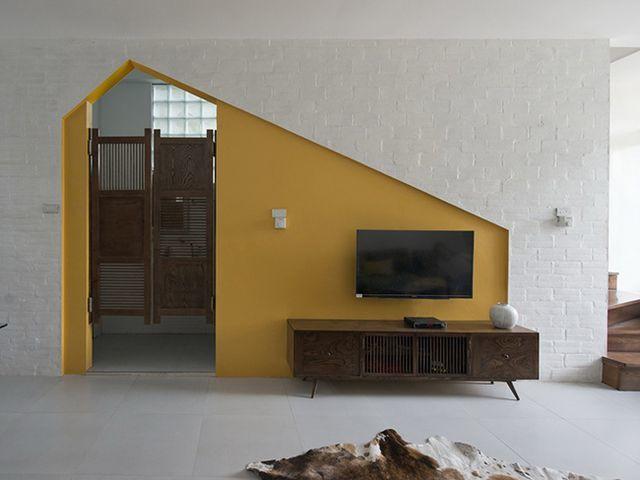 Góc đặt tivi và tủ ly được sơn màu vàng tạo điểm nhấn và phân tách không gian giúp tạo cảm giác rộng hơn.