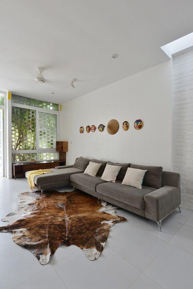 Phòng khách hiện đại với bộ sofa màu ghi sáng và thảm trải sàn màu da bò.