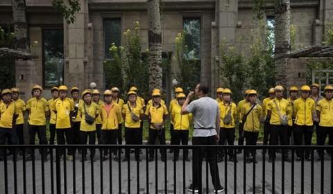 Nhân viên Meituan họp giao ban vào buổi sáng trên một con phố ở Bắc Kinh. Ảnh: AFP.