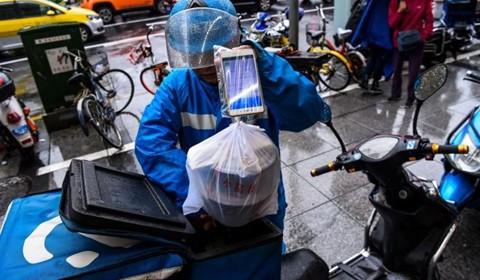 Tài xế giao hàng làm việc bất chấp thời tiết nắng mưa. Ảnh: AFP.