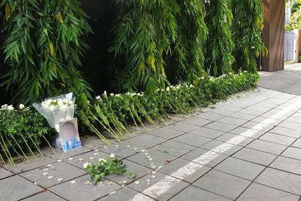 Người dân lặng lẽ đặt bông cúc trắng trước cổng trường Gateway để tưởng nhớ bé trai tử vong thương tâm trên xe đưa đón - Ảnh 1.