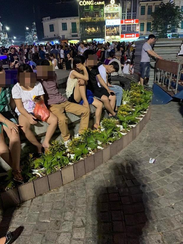 Bức xúc hình ảnh hàng chục người ngồi bên đài phun nước phố đi bộ Hồ Gươm, thản nhiên đạp chân thẳng lên hàng hoa trang trí - Ảnh 4.