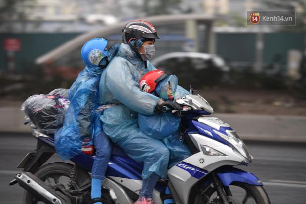 Trẻ nhỏ trùm chăn, khoác áo mưa chật vật theo chân bố mẹ rời Thủ đô về quê ăn Tết - Ảnh 1.